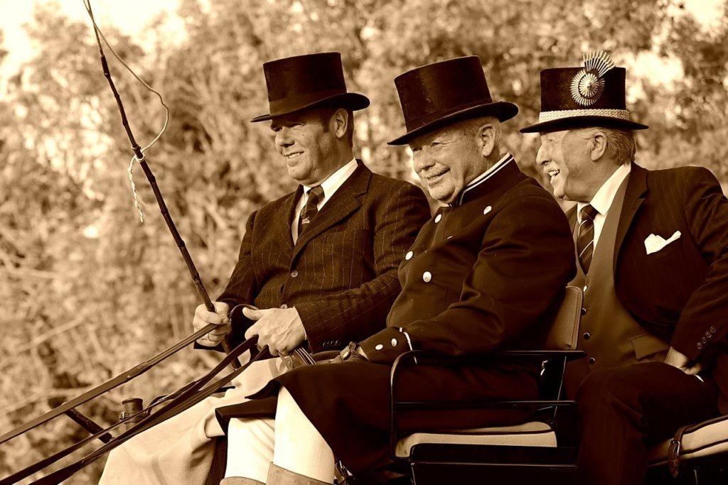 Bild dreier Kutscher auf einem Kutschbock mit Anzug, Zylinder und Peitsche