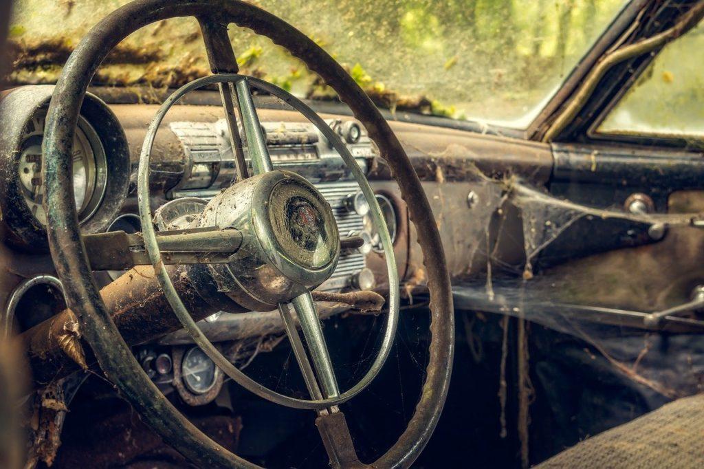 Bild einer schmutzigen Inneneinrichtung eines verrottenden Autos mit Spinnennetzen